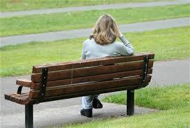 Ensam kvinna på parkbänk