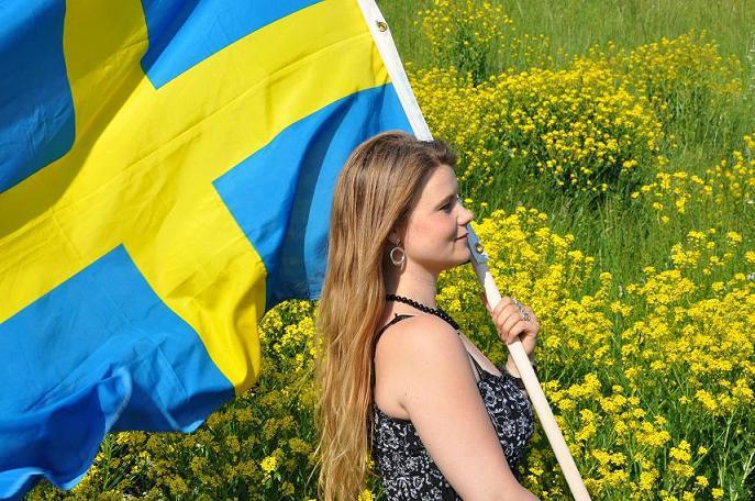 Tanja Bergkvist med svensk flagga. Profil.